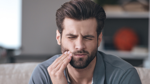 Man Holding Cheek From Pain | Gentry Dental